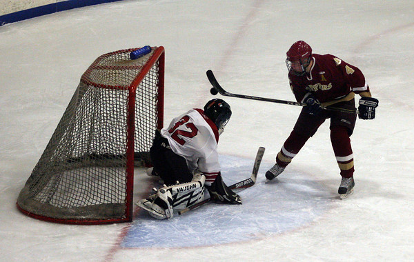 Gloucester: Newburyport's Cameron Roy knocks the puck past Gloucester goalie Mike Bresnahan at the Talbot Rink last night. Photo by Kate Glass/Newburyport Daily News