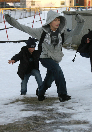 Gloucester: Dylan Lessard shows his friend, JJ McKenna, the best way to climb up the hill at Mattos Field without falling down on the ice after shool yesterday. Photo by Kate Glass/Gloucester Daily Times