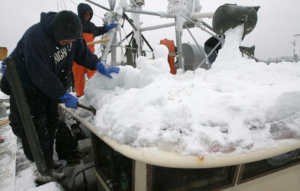 Gloucester: Captain Ron Davis hammers ice off the wheelhouse of the Michael & Kristen yesterday. The crew had chiseled away much of the ice while at sea, but could do a better job in port. Photo by Kate Glass/Gloucester Daily Times