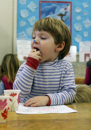 Essex: Oliver Rodi munches on a fist full of popcorn at the TOHP Burnham Library during story hour on Wednesday. Wednesday was National Popcorn Day and the children listened to stories involving popcorn and received the popular treat as a snack. Photo by Kate Glass/Gloucester Daily Times