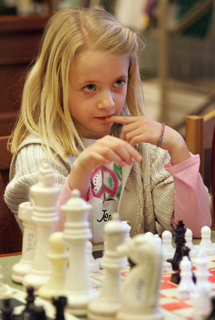 """Manchester: Jennifer O'Neil, 7, thinks about her next move while playing chess at the Manchester Public Library Thursday afternoon.  This is Jennifer's third week learning to play chess at the library and is beginning to understand all the rules although she did say, """"I have no idea what I am doing"""" at one point in the game.  Mary Muckenhoupt/Gloucester Daily Times"""