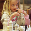 "Manchester: Jennifer O'Neil, 7, thinks about her next move while playing chess at the Manchester Public Library Thursday afternoon.  This is Jennifer's third week learning to play chess at the library and is beginning to understand all the rules although she did say, ""I have no idea what I am doing"" at one point in the game.  Mary Muckenhoupt/Gloucester Daily Times"