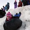 Manchester: Sylvie Oldeman uses a trash bag to help her gain speed as she and her friends in the Hornet's After School Program slide down the snow piles behind Manchester Memorial Elementary School yesterday. Photo by Kate Glass/Gloucester Daily Times