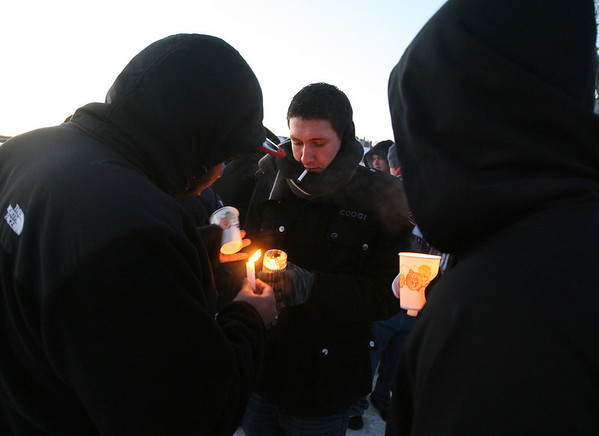 Gloucester: Dillon Renard helps friends light candles during a vigil on the Boulevard in memory of Nate Holscher, who was killed in a car accident on Route 128. Photo by Kate Glass/Gloucester Daily Times