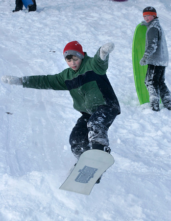 Rockport: Gus Campbell flies off a jump on his snowboard as Bennet Wilson looks on at Evans Field on Friday. Photo by Kate Glass/Gloucester Daily Times