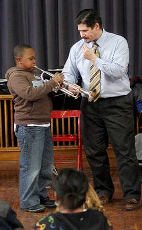 Gloucester: Rob Bradshaw of the Cape Ann Symphony teaches Christian Baptiste, a fifth grade student at Beeman Memorial Elementary School, how to play the trumpet during a demonstration at the school on Tuesday. Members of the symphony are visiting grades 4 and 5 throughout Cape Ann prior to the Cape Ann Symphony Youth Concert, which will be held on January 21st. Photo by Kate Glass/Gloucester Daily Times
