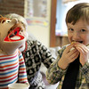 Gloucester: Kellen Moran, a pre-kindergartener at the Eastern Point Day School, eats his munchkin as Alphabet Al asks for a bite during a teddy bear tea party with pre-K teacher Tami Cronin Wednesday morning. The tea party was held as part of Experience Eastern Point Day School Week where students 3 to 12 years old are invited to tour the school and participate in classes.  Mary Muckenhoupt/Gloucester Daily Times