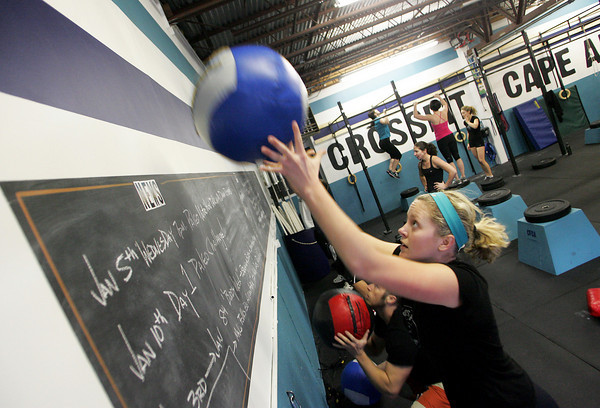 Gloucester: Megan Goddard throws a fourteen pound ball up against the wall during an half hour workout at Crossfit Cape Ann. Mary Muckenhoupt/Gloucester Daily Times