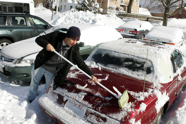 Manchester: Joe Perna cleans off his car with a mop saying his ice scraper has already broke this winter from all the use in the town parking lot behind Manchester Town Hall Thursday morning.   Perna said even on the hottest day of the summer he won't complain about the heat after this winter. Mary Muckenhoupt/Gloucester Daily Times