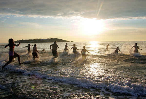 Gloucester: People run into the water for the annual New years Day swim at Good Harbor Beach Saturday at 8 a.m. Mary Muckenhoupt/Gloucester Daily Times