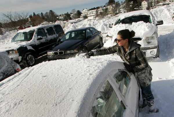 Manchester: Emily Perrier of Manchester uses just her hands to clear off her car in the town lot behind Manchester Town Hall Thursday morning. Mary Muckenhoupt/Gloucester Daily Times