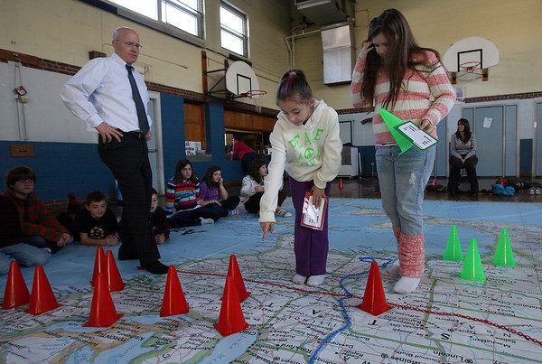 Gloucester: East Gloucester Elementary School Principal Greg Bach watches as Teala Bailey helps her 4h grade classmate, Jamie Lee Frontiero, find Chicago during a lesson using National Geographic's Giant Map of North America. The program was brought in by the East Gloucester Elementary School PTO and all grades will be working on different lessons with the map. Photo by Kate Glass/Gloucester Daily Times