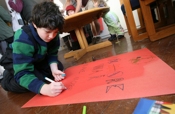 """Rockport: Sean Whelan, 10, of Rockport draws a sign saying """"No More War"""" before the 23rd Annual Martin Luther King Jr. Walk yesterday, which is organized by the Rockport Unitarian Universalist Church. Photo by Kate Glass/Gloucester Daily Times"""