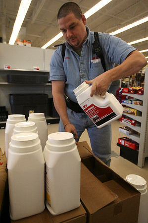 Gloucester: Shawn Vincent restocks ice melt at ACE Hardware yesterday as people stocked up on items to help deal with the snowstorm. Photo by Kate Glass/Gloucester Daily Times