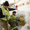 Gloucester: Firefighters William Doucette and John Nicastro put on a tall orange marker to help firefighters find the hydrants in the the tall snow banks Friday afternoon. The Fire department has been working to shovel out all hydrants that were burried in snow and ice from the last snow storm which dumped over a foot of snow on Cape Ann. Mary Muckenhoupt/Gloucester Daily Times