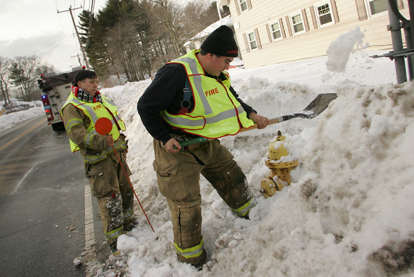 Gloucester: Firefighter William Doucette digs out a hydrant on Essex Avenue before John Nicastro puts on a tall orange marker to help firefighters find the hydrants in the the tall snow banks Friday afternoon. The Fire department has been working to shovel out all hydrants that were burried in snow and ice from the last snow storm which dumped over a foot of snow on Cape Ann. Mary Muckenhoupt/Gloucester Daily Times
