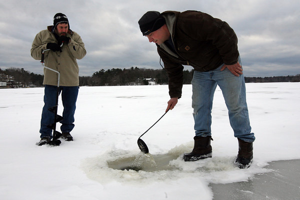 Essex: Peter Libro, left, watches as Steve Corbett cleans out a hole for ice fishing at Chebacco Lake yesterday afternoon. Although they got a late start, they did catch some pickerel. Photo by Kate Glass/Gloucester Daily Times