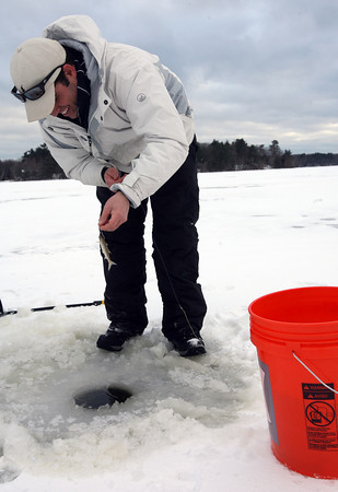 Essex: Collin MacKenzie baits a hook for ice fishing on Chebacco Lake on Tuesday. Photo by Kate Glass/Gloucester Daily Times