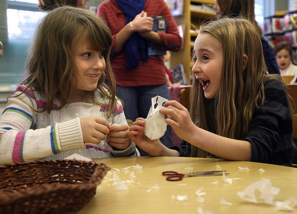 Essex: Alanna Fitzgerald, left, and Hannah Burnett smile as they open snowflakes they made during the Snowflake Festival at the TOHP Burnham Library on Thursday. Photo by Kate Glass/Gloucester Daily Times