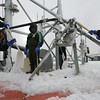 Gloucester: Jesse Grissom, Basilio Valerio, and Jose Godinho assist the crew of the Michael & Kristen with removing ice from the boat while docked at the Jodrey State Fish Pier yesterday. The crew had been out in sub zero temperatures and any water that washed over the vessel instantly froze. Photo by Kate Glass/Gloucester Daily Times