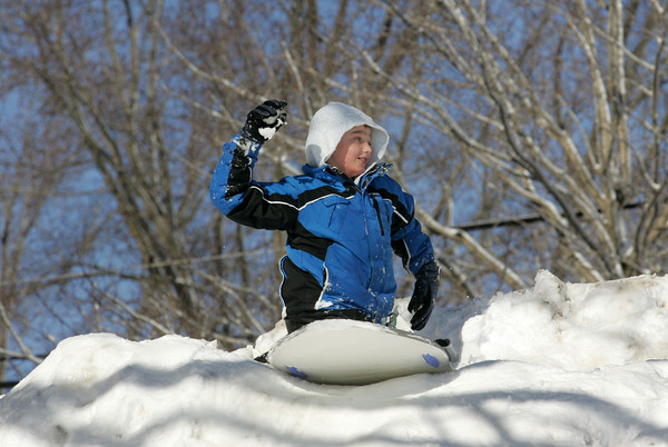 Essex: Jackson Byrne, 10, winds up a snowball to thow at his mother while sledding behind TOHP Burnham Library in Essex Thursday morning. Mary Muckenhoupt/Gloucester Daily Times