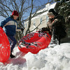 Gloucester: Jillian Tierney, 9, and her brother Noah, 11, climb to the top of the snow bank that is in their front yard of their Middle Street home go  sledding with their mom and sister Grace, 4, while taking advantage of another snow day Thursday afternoon. Mary Muckenhoupt/Gloucester Daily Times