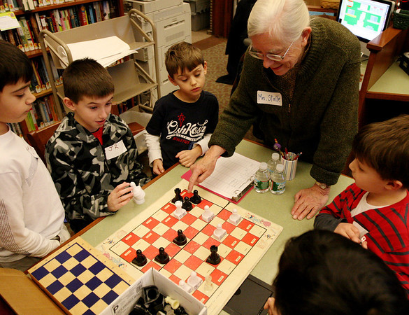 ALLEGRA BOVERMAN/Staff photo. Gloucester Daily Times. Manchester: <br /> Clockwise around the chess board, from lower left, are: Jake Giarratana, 9, JR Cravotta, 10, and Luke Giarratana, 6, all of Danvers, teacher Sandra Stolle, Owen O'Leary, 6, and Giuseppe Tra, 7, both of Manchester. They are taking part in the first of three Chess Club workshops held at the Manchester Public Library in January by Stolle, of Wenham. The free workshops will be held next on Mon. Jan. 23 and Mon. Jan. 30, and may also extend into February. About a dozen children were there  learning basic chess rules and strategy on Monday afternoon.