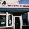 ALLEGRA BOVERMAN/Staff photo. Gloucester Daily Times. Gloucester: Rosario Maletti, owner of DeMarco's Cleaners, replaces a light bulb at the Washington Street location on Wednesday afternoon.