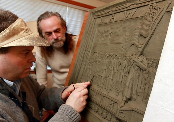ALLEGRA BOVERMAN/Staff photo. Eagle-Tribune. Gloucester: Daniel Altshuler, left, of Gloucester, is working on two bronze plaques that will commemorate the Bread and Roses Strike of 1912 and be placed in Lawrence's Campagnone Common a few hundred feet west of City Hall. David Meehan, a retired art teacher at Lawrence High School and a co-chair of the monument committee, is visiting with him on Wednesday.