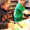 William Kirby, 8, of Manchester, uses watercolors to try to replicate the fluid appearance of the colorful aurora borealis on paper at a hands-on science workshop sponsored by the Manchester Public Library on Saturday morning. Jesse Poole/Gloucester Daily Times Jan. 7, 2012