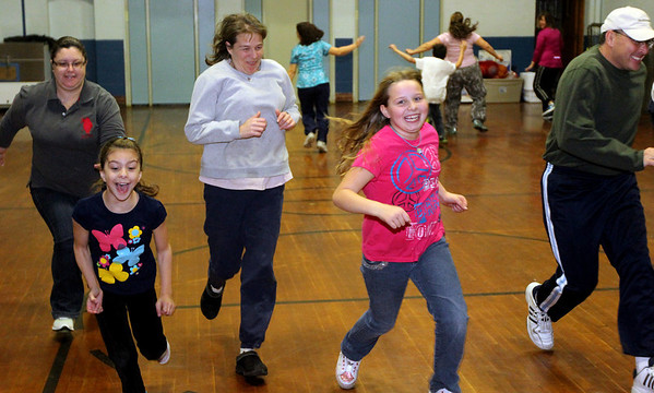 "ALLEGRA BOVERMAN/Staff photo. Gloucester Daily Times. Gloucester: East Gloucester Elementary School Physical Education/Health teacher Barrett Rounds hosted a Family Fitness Night at the school gym for third graders and their parents on Tuesday evening. Parents and their kids played games and exercised together and learned more about how physical education factors into the school day and how it positively impacts other academic pursuits. Playing ""True v. False"" in front, from left are: third graders Lia Clara and Laura Ryan. In back, from left are: Silvana DiNiz, Clara's mom, Kristin Ryan, Laura's mom, and James Barrett, running after his daughter Sophia Barrett (not shown). They played a variety of other games, including Snowball, a spinoff of dodgeball, and Asteroids."