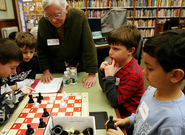 ALLEGRA BOVERMAN/Staff photo. Gloucester Daily Times. Manchester: Clockwise around the chess board, from lower left, are: Jake Giarratana, 9, JR Cravotta, 10, and Luke Giarratana, 6, all of Danvers, teacher Sandra Stolle, Owen O'Leary, 6, and Giuseppe Tra, 7, both of Manchester. They are taking part in the first of three Chess Club workshops held at the  Manchester Public Library in January by Stolle, of Wenham. The free workshops will be held next on Mon. Jan. 23 and Mon. Jan. 30, and may also extend into February. About a dozen children were there  learning basic chess rules and strategy on Monday afternoon.