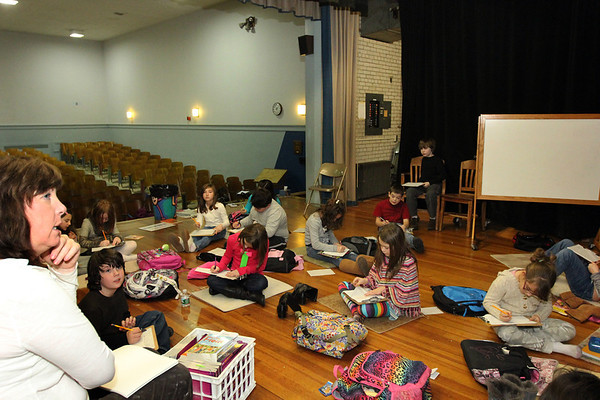ALLEGRA BOVERMAN/Staff photo. Gloucester Daily Times. Gloucester: Eileen Egan's third grade class has relocated temporarily to the auditorium stage while her classroom's heat and various burst pipes are repaired. They were writing essays on Thursday afternoon.