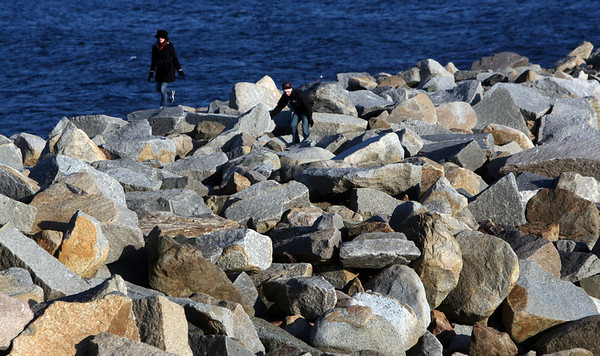 """ALLEGRA BOVERMAN/Staff photo. Gloucester Daily Times.Rockport: Marzieh Talebi, left, visiting from the Netherlands, and Miguel de Corral, of Grafton, scramble over the rocks at the Bearskin Neck breakwater on Tuesday afternoon while visiting Rockport. De Corral said that whenever he and his family have visitors, they always like to take them to Rockport because it's such """"a quaint, lovely town,"""" he said, and very representative of New England. They then were going to explore Gloucester."""
