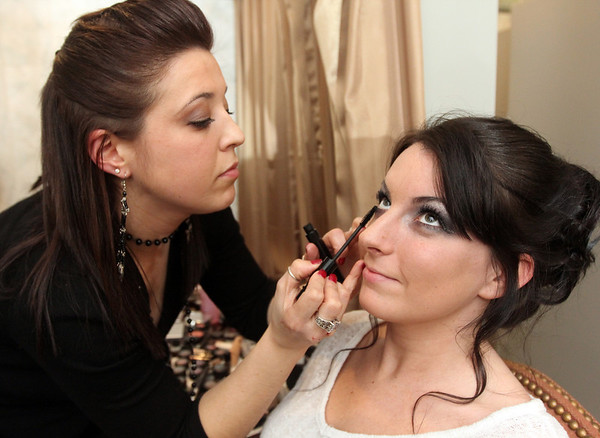 ALLEGRA BOVERMAN/Staff photo. Gloucester Daily Times. Gloucester: Over 1000 people attended the fourth annual Cruiseport Gloucester Bridal Show and Wedding Expo on Thursday evening. EnVogue Salon employee Amra Sclafani of Gloucester, left, does the makeup for model Stephanie Daigle of Rockport before the bridal fashion show.