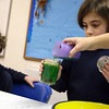 "ALLEGRA BOVERMAN/Staff photo. Gloucester Daily Times. Gloucester: During the ""Kids Cook"" after school session at Eastern Point Day School on Wednesday, students made edible ""Jell-O Aquariums,"" made of Jell-O in their choice of color, granola and Swedish Fish candy. After-School programs director Crystal Stal pours green Jell-O into the Mason jar of Anita Magee, 7, as Thurston Eck, 6, left, looks on."