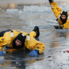 ALLEGRA BOVERMAN/Staff photo. Gloucester Daily Times. Gloucester: Gloucester Firefighters Nick Ouellette, front, and Adam deBrigard practice rescues from icy pond water, at Cape Ann Sportsman's Club on Tuesday afternoon.