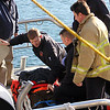 ALLEGRA BOVERMAN/Staff photo. Gloucester Daily Times. Gloucester: Gloucester fire personnel and U.S. Coast Guard personnel get ready to transport Leo Vitale, a worker who fell off a dock and onto a boat below at BASE Gloucester Seafood Exchange on Monday afternoon. He was transported to Beverly Hospital.