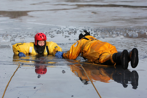 ALLEGRA BOVERMAN/Staff photo. Gloucester Daily Times. Gloucester: Gloucester Firefighter Nick Ouellette, left, gets instructions on how to pull himself up and out of icy pond water, with and without using ice picks,  from Fran Clarke of the Massachusetts Fire Academy at Cape Ann Sportsman's Club on Tuesday afternoon.