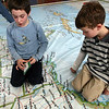 """ALLEGRA BOVERMAN/Staff photo. Gloucester Daily Times. Gloucester: The North American National Geographic Giant  Traveling Map is on display and in use at West Parish Elementary School until Jan. 12. The Physical Education teacher, Amy Elliot, who used to teach geography and social studies, has been incorporating the map into her exercise curriculum. On Thursday afternoon, the first grade  class there was not only scrambling around and exploring the map, but teaming up with a partner to find states and cities on the giant map - that fills the gym - as though  they were postal carriers """"delivering"""" messages to those locations. Max Vieira, left, and Tyler Weed search for Denver. The map will travel next to East Gloucester Elementary School."""