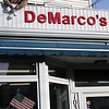 ALLEGRA BOVERMAN/Staff photo. Gloucester Daily Times. Gloucester: Rosario Maletti, owner of DeMarco's Cleaners, changes a light bulb on the sign at the Washington Street location on Wednesday afternoon.