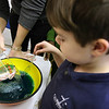 "ALLEGRA BOVERMAN/Staff photo. Gloucester Daily Times. Gloucester: During the ""Kids Cook"" after school session at Eastern Point Day School on Wednesday, students made edible ""Jell-O Aquariums,"" made of Jell-O in their choice of color, granola and Swedish Fish candy. After-School programs director Crystal Stal pours cool water into boiling water and Jell-O mix to make an ocean-like color as Sebastian Lovasco, 7, helps stir it up."