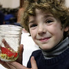 "ALLEGRA BOVERMAN/Staff photo. Gloucester Daily Times. Gloucester: During the ""Kids Cook"" after school program on Wednesday at Eastern Point Day School, students made edible  ""Jell-O Aquariums,"" made of Jell-O in their choice of color, granola and Swedish Fish candy. Thurston Eck, 6, shows how his fish and the ""ocean bottom"" look before green Jell-O was poured in."