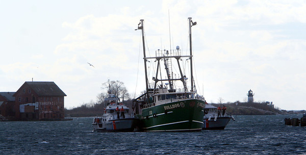 ALLEGRA BOVERMAN/Staff photo. Gloucester Daily Times. Gloucester: On Friday morning Coast Guard boats escort the fishing boat Bulldog into Gloucester and docked it behind Cruiseport Gloucester after it was disabled in New Hampshire waters on Thursday evening. The boat's engine shaft was broken and needs repair.