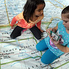 "ALLEGRA BOVERMAN/Staff photo. Gloucester Daily Times. Gloucester: The North American National Geographic Giant  Traveling Map is on display and in use at West Parish Elementary School until Jan. 12. The Physical Education teacher, Amy Elliot, who used to teach geography and social studies, has been incorporating the map into her exercise curriculum. On Thursday afternoon, the first grade  class there was not only scrambling around and exploring the map, but teaming up with a partner to find states and cities on the giant map - that fills the gym - as though  they were postal carriers ""delivering"" messages to those locations. The map travels next to East Gloucester Elementary School. Searching for Arkansas are first graders Chandra Lavery, left, and Mia Contilli."