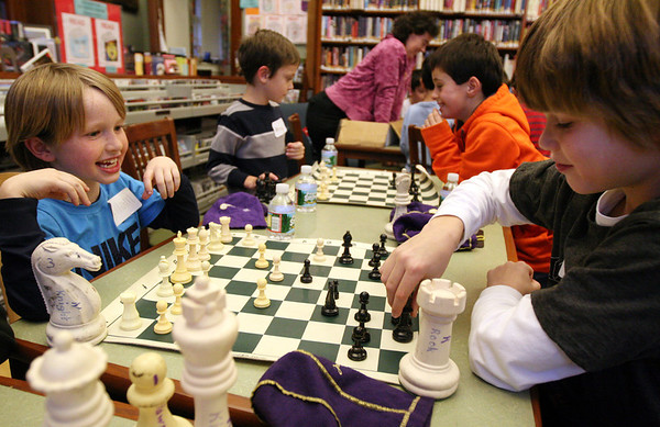 ALLEGRA BOVERMAN/Staff photo. Gloucester Daily Times. Manchester: From left are William Kirby, 8, playing against Max Elwell, 9, and down the table from them are Remsen Demeo, 7, left, playing against William Pollock, 9. They are taking part in the first of three Chess Club workshops held at the Manchester Public Library in January by teacher Sandra Stolle of Wenham. The free workshops will be held next on Mon. Jan. 23 and Mon. Jan. 30, and may also extend into February. About a dozen children were there  learning basic chess rules and strategy on Monday afternoon.