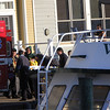 ALLEGRA BOVERMAN/Staff photo. Gloucester Daily Times. Gloucester: Gloucester fire personnel, with the help of U.S. Coast Guard personnel, got  ready to transport Leo Vitale, a worker who fell off a dock onto a boat below at BASE Gloucester Seafood Exchange on Monday afternoon. He was put into a waiting ambulance at The Gloucester House and was taken to Beverly Hospital.
