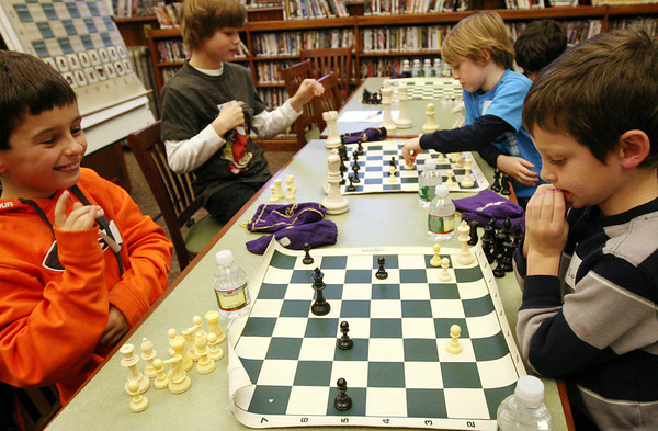 ALLEGRA BOVERMAN/Staff photo. Gloucester Daily Times. Manchester:  In front, from left are WIlliam Pollock, 9 playing chess against Remsen Demeo, 7. Behind them from left are Max Elwell, 9, and William Kirby, 8. They are taking part in the first of three Chess Club workshops held at the Manchester Public Library in January by teacher Sandra Stolle of Wenham. The free workshops will be held next on Mon. Jan. 23 and Mon. Jan. 30, and may also extend into February. About a dozen children were there learning basic chess rules and strategy on Monday afternoon.