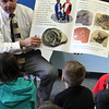 ALLEGRA BOVERMAN/Staff photo. Gloucester Daily Times. Gloucester: For the third grade science unit on rocks and minerals and sediment at Veterans Memorial Elementary School, students are learning about how fossils are formed. Teacher Steve Mirandi discusses fossils and geologic time with the students after they learned how to make their own fossils from educators from the Gloucester Maritime Center on Thursday afternoon.