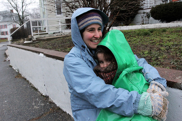 "ALLEGRA BOVERMAN/Staff photo. Gloucester Daily Times. Gloucester: Susan Sappia and her daughter Sabina Sappia, 4, of Angle Street sit on a stool across from their house waiting for Sabina's older brother to return home from school on Thursday afternoon. Even though the weather was blustery, cold and rainy, Susan said that she wants to ""get them outside no matter the weather,"" every single day, ""So we bundled up and came outside for a bit. You do silly things for your kids."""